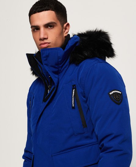 Superdry men\\\'s Premium Ultimate Down jacket. Stay warm in style this season with the Premium Ultimate Down jacket, with a 90/10 premium duck down filling and a very high fill power rating this jacket will make sure you\\\'re ready to take on those colder days. It features a detachable hood with faux fur trim, double layer zip fastening and hook and loop fastening for extra protection against the cold. The jacket also features eight front pockets and one inside pocket, perfect for keeping your valua
