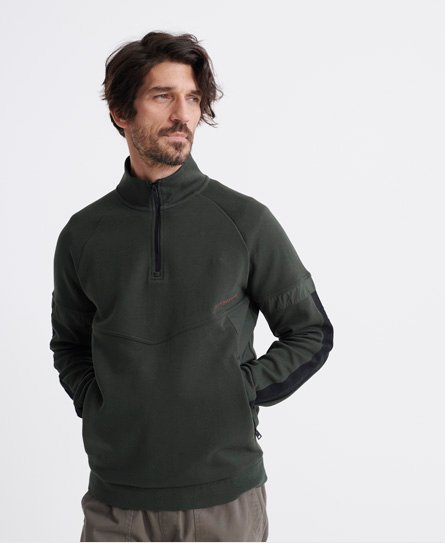 Superdry men\\\'s Urban Tech half zip track top. This overhead track top features a half zip fastening, a front pouch pocket with zip fastenings and ribbed cuffs and hem. Finished with Superdry branding down both arms and a rubber Superdry logo on the chest. Slim fit